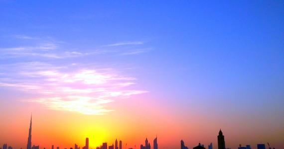 صورة تظهر سماء دبي وأفقها ومبانيها والشمس خلفها.